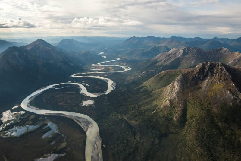 aerial view of meandering river through mountains